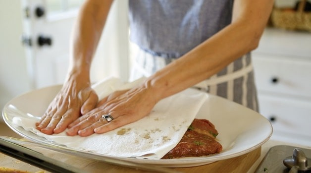 patting a marinated flank steak dry before grilling