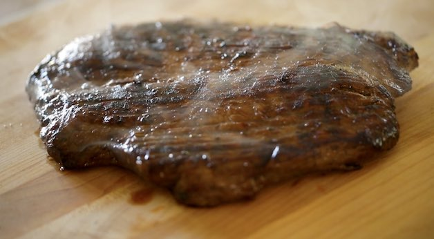 Grilled Flank steak resting on a cutting board to cool