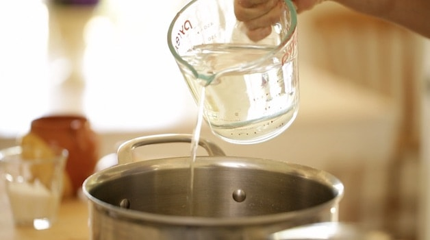 Adding water from a glass pitcher into a pot on a cooktop