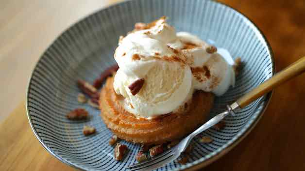 Churro Sundae on a blue plate with Whipped Cream, cinnamon and nuts