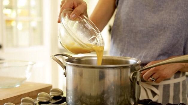 Adding beaten egg to a pot for a churro recipe