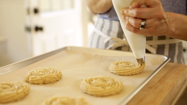 piping churron dough onto parchment lined cookie sheets from a pastry bag