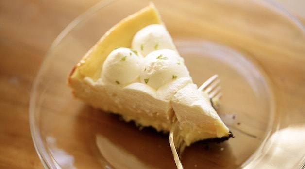 a fork taking a bite out of a key lime pie cheesecake on a glass plate
