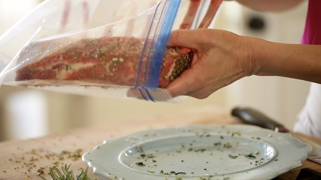 placing rack of lamb, seasoned with rosemary, into a ziplock bag