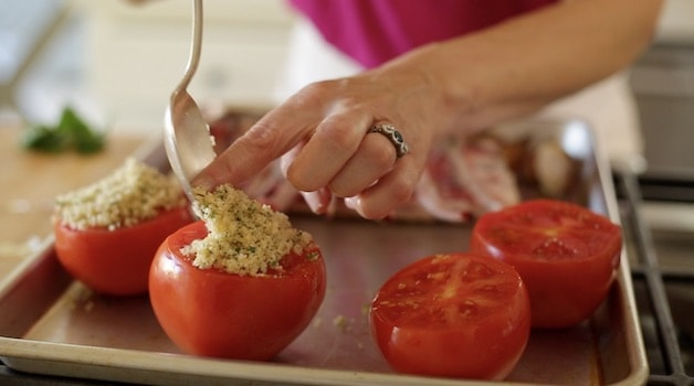 Placing bread crumbs on a tomato on a sheet pan