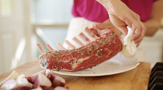 Brushing off rosemary from a rack of lamb before searing