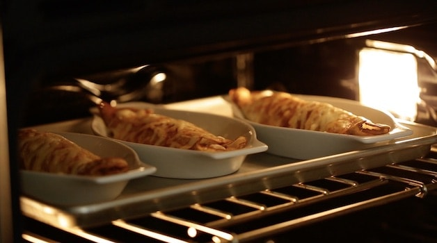 Three gratin dishes of mushrrom and chicken crepes in the oven under the broiler