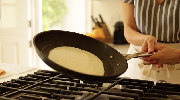 Swirling pan around to distribute crepe batter