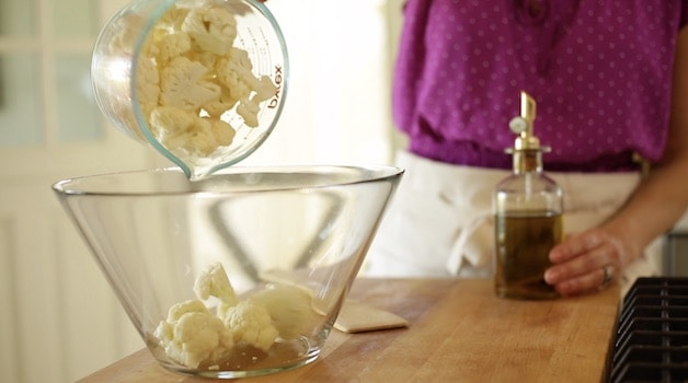 Adding raw cauliflower florets to a glass bowl