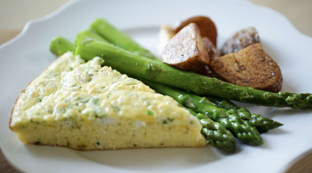 A slice of Egg Bake Casserole with roasted potatoes and asparagus