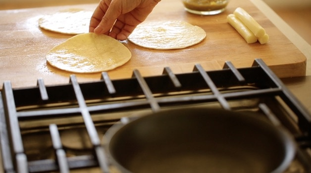 adding tortilla that has been softened with olive oil to a pan to heat