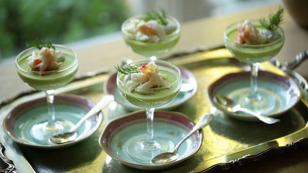 A group of champagne coupes filled with sweet pea panna cotta, topped with cream and crab and set on saucers on a silver tray