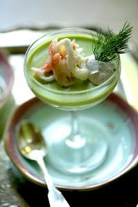 Vertical image of a savory panna cotta with sweet pea and king crab, in a 1930's style champagne coupe