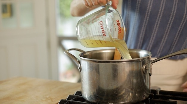 adding chicken broth to a sauce pan