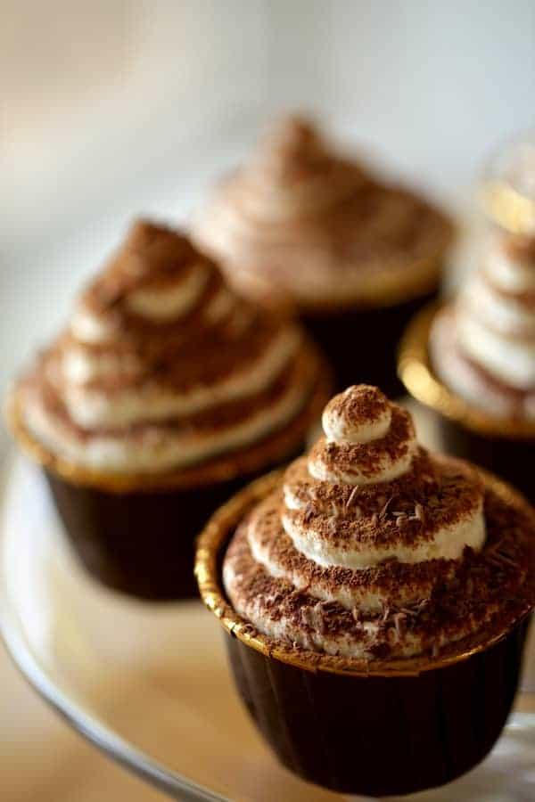 vertical image of Tiramisu cupcakes on a glass cake stand