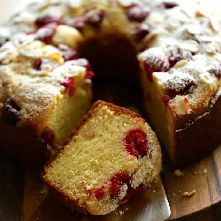 Raspberry Almond cake on a board with a slice taken out