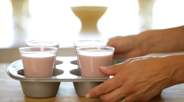 Cups of Strawberry Panna Cotta placed into a jumbo muffin tin and used as a tray