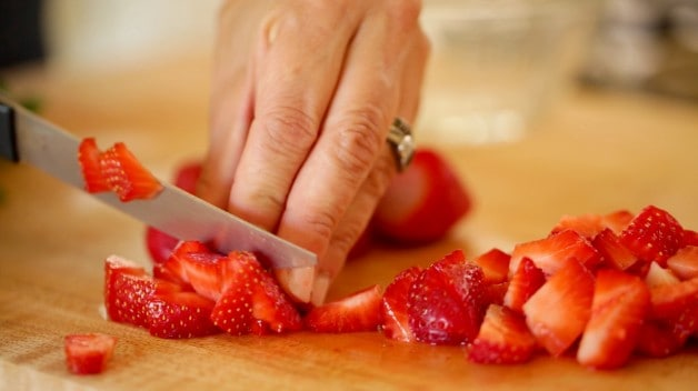 A person chopping strawberries on cutting board