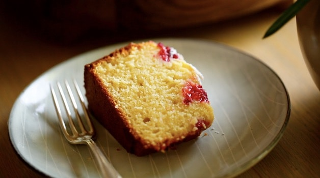 A slice of a raspberry almond cake on a gray plate with fork