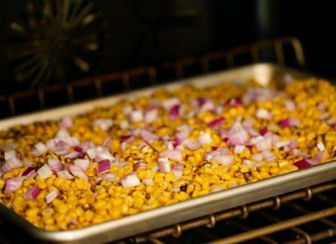 Corn and purple onion on baking sheet