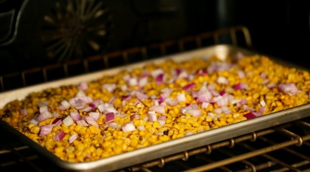 Corn and red onion on baking sheet in the oven