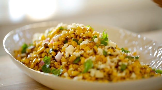 Queso Fresco Cheese crumbled on top of a corn salad in a white platter