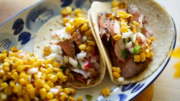 Corn Salad sprinkled over tacos on white and blue plate