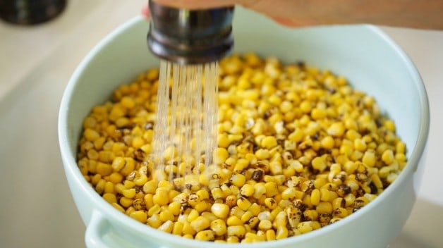 Rinsing charred corn in a blue colander