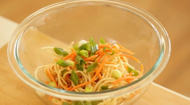 bowl of carrots, green onions and noodles for sesame mixture