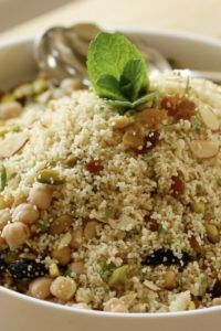 Couscous salad in a white bowl with dried fruits, buts and mint