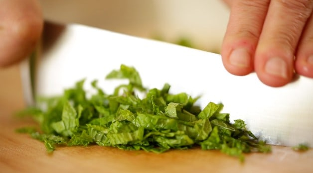 chopping mint on a cutting board with a chef knife
