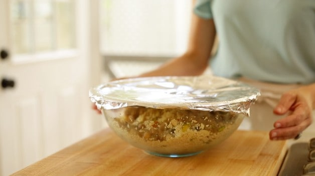 Couscous salad in clear bowl with plastic wrap