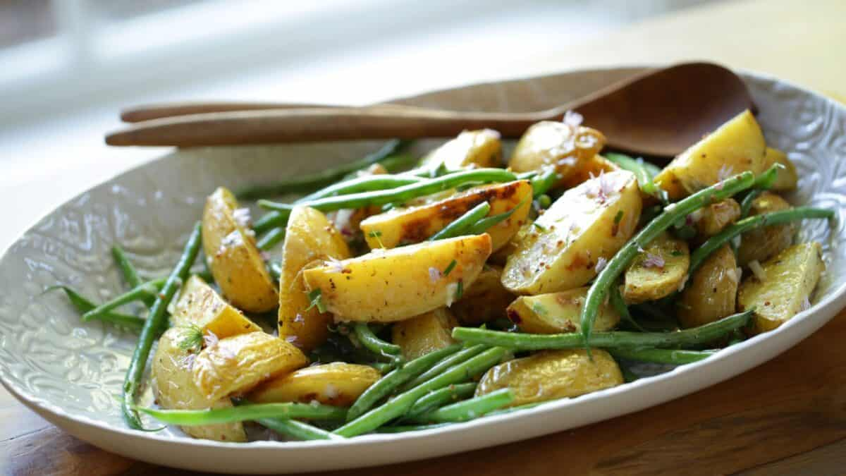 Potato salad with no mayo on a platter with green beans and vinagrette