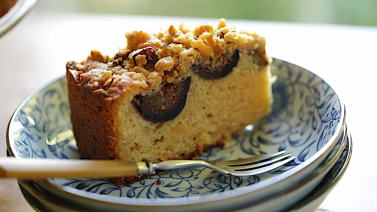 a slice of fig cake on a blue plate with a fork