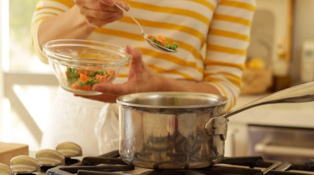 Adding frozen peas and carrots to pot