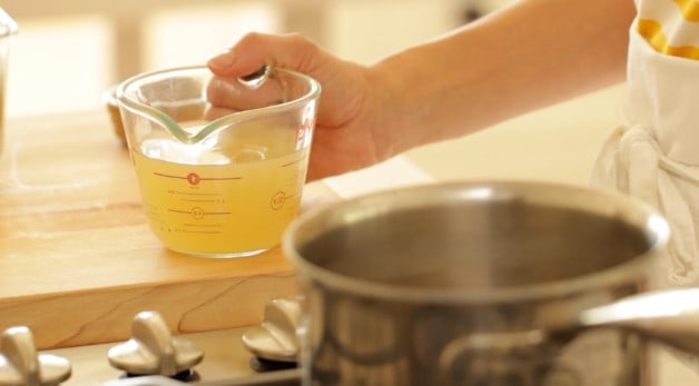Pyrex pitcher of chicken broth and pot