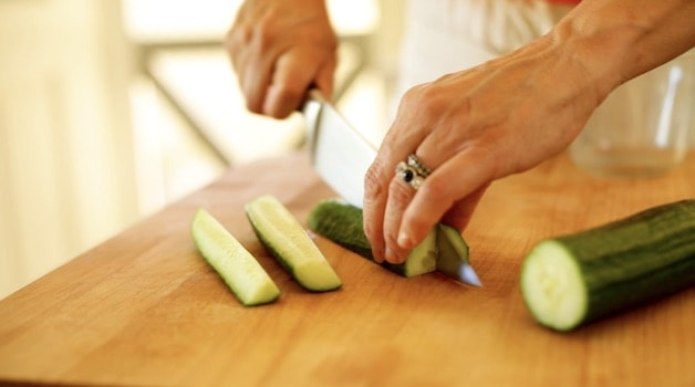 Slicing an English cucumber on a cutting board