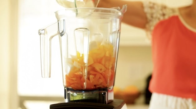 Adding white onion to a blender filled with tomatoes and yellow peppers