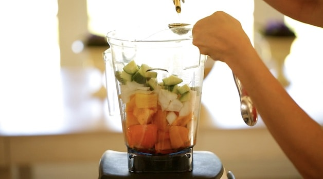 Adding olive oil to a blender filled with vegetables