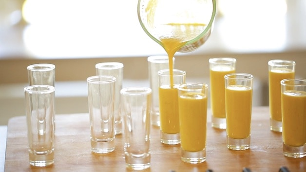 Pouring yellow gazpacho soup into small shot glasses