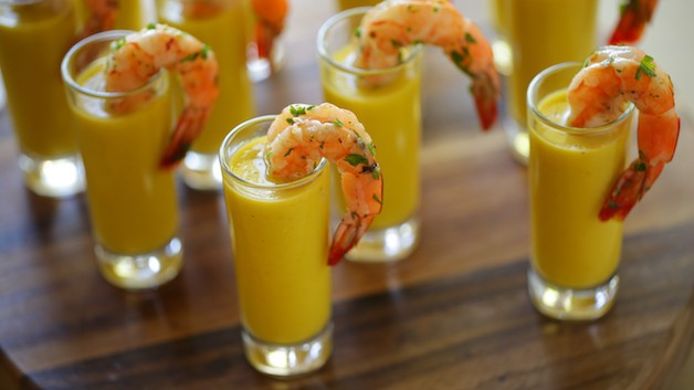 Yellow Gazpacho soup in shot glasses with shrimp