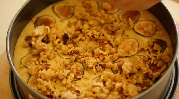 A batter of fig cake topped with crumb topping ready for the oven