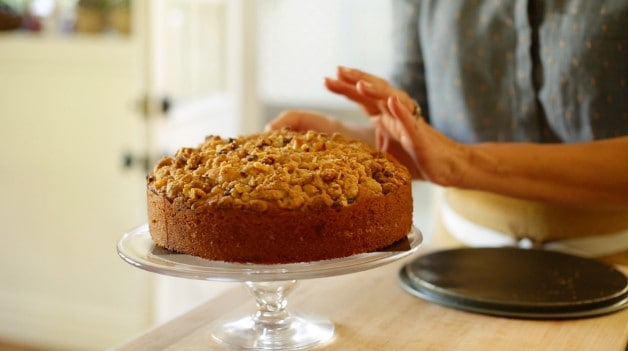 Placing a fig cake on a glass cake stand with a cake lifter