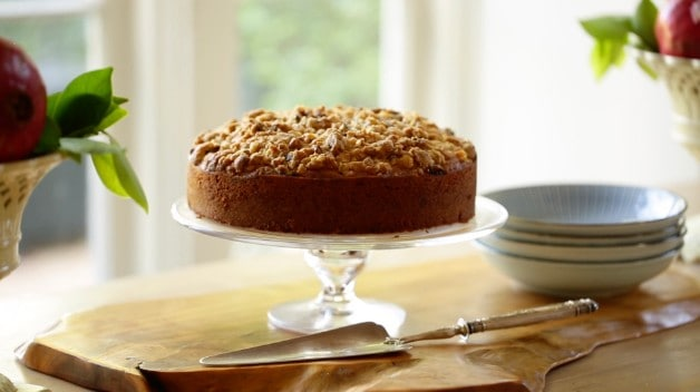 A fresh Fig Cake with Crumb Topping on a Glass Cake Stand with Silver Cake Server