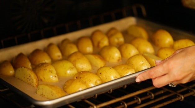 Potatoes sliced on baking sheet for No-Mayo Potato Salad Recipe
