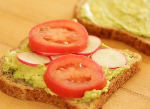 Avocado mixture on bread with sliced radish and tomato