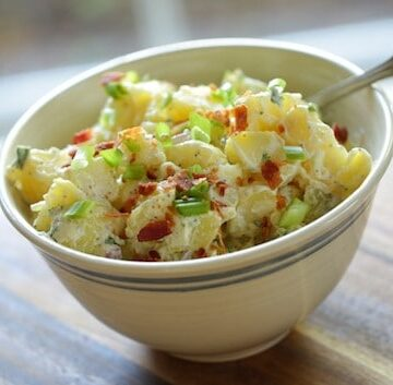 Close up of Traditional Potato Salad with bacon and green onions in bowl with a spoon