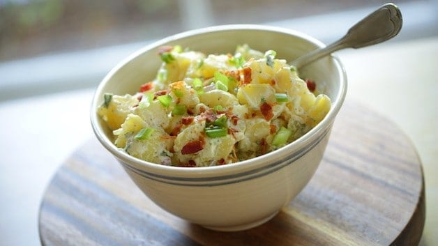 Close up of Traditional Potato Salad in white bowl with spoon