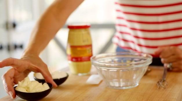 Adding mayonnaise to mixing bowl to make potato salad