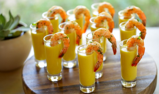 12 shot glasses on a cutting board filled with gazpacho soup and shrimp tails